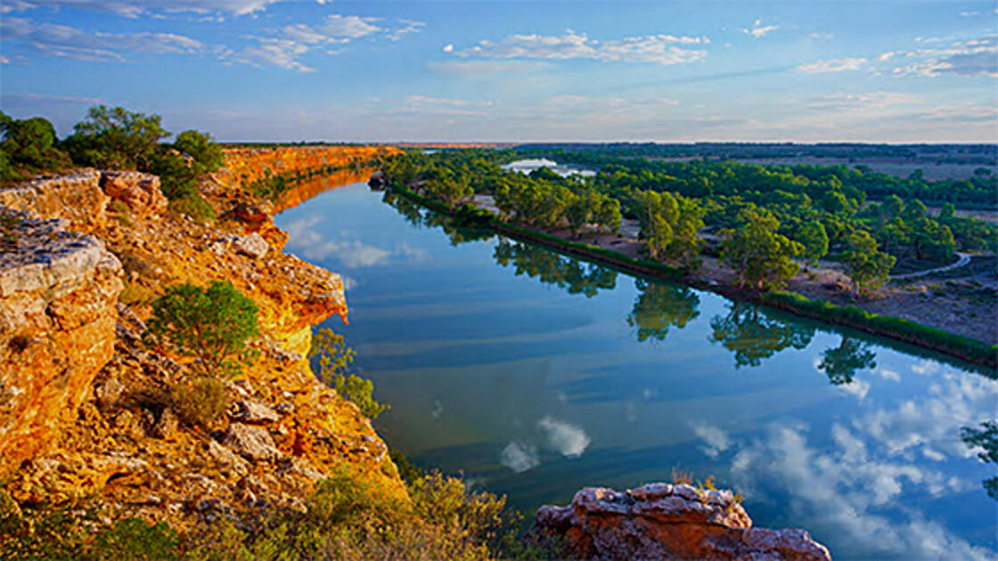 Expansive view of a river. With red rock cliffs on the left-hand side and green land and trees on the right-hand side.
