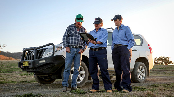 Two NRAR officers showing a landowner some information about water rules on a tablet. They are standing in front of an SUV vehicle in and open field.