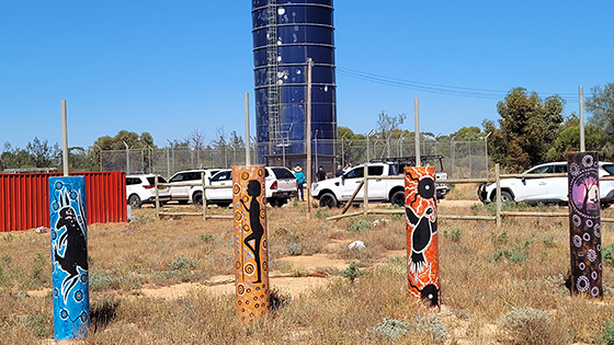 Namatjira Raw Water Tank in the background, with 4 painted Aboriginal artworks on poles in the foreground.